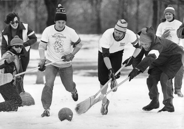 An outdoor broomball game in action in the snow.