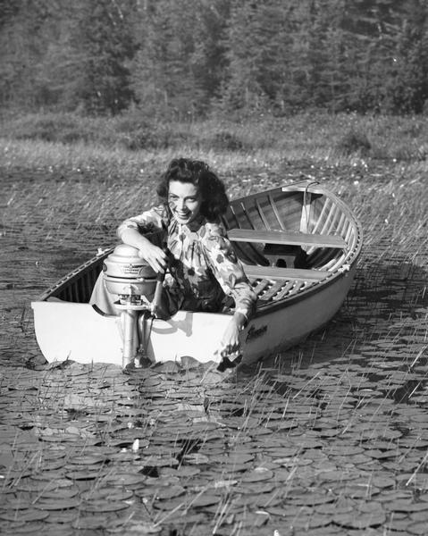 An Evinrude boat motor advertisement with woman posing in boat.