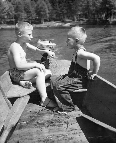 Two boys, probably brothers, using a small boat with outboard motor.