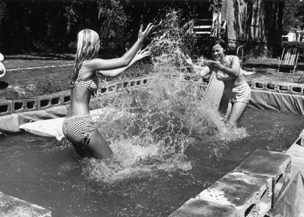 To escape the heat, teenage girls have a water fight in the backyard pool they built.