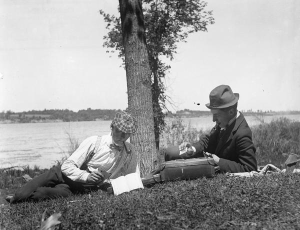 Two men smoking pipes and playing cards in the grass along a riverbank.