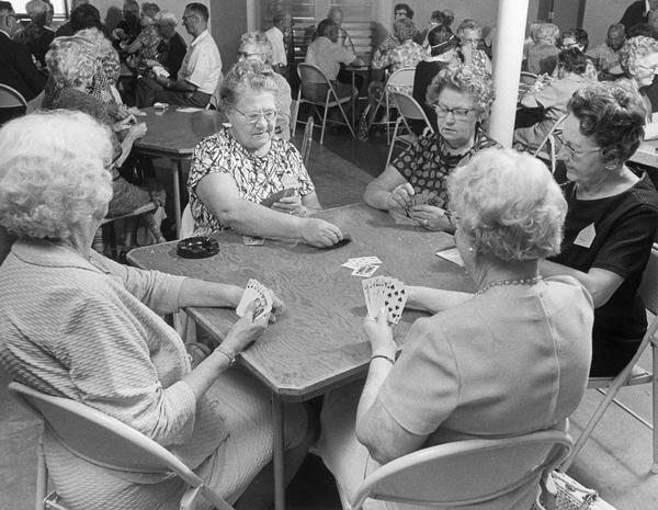 Elderly women sit around a card table and play cards at a new senior center.