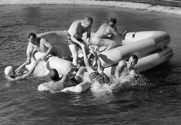 A rubber raft serves as the launching point for diving and other water play on a hot summer day.