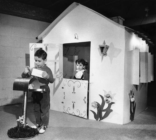 A young girl watches out the door of her playhouse while a young boy retrieves letters from the play mailbox.