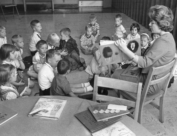 A librarian reads a children's book aloud to young boys and girls.