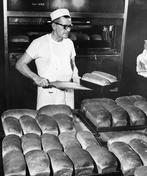 A baker removes multiple loaves of bread from the oven for consumption in both bakery and restaurant.