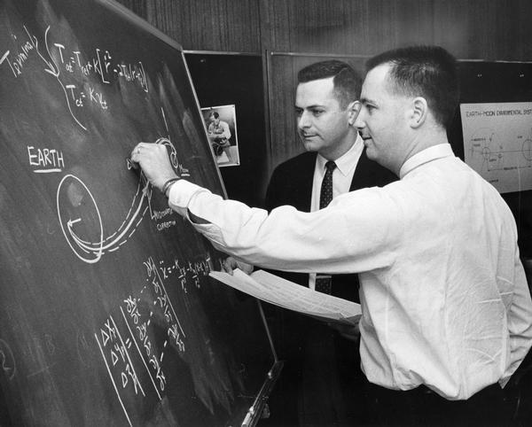 Lunar trajectory paths and computations on a blackboard are discussed by employees of Milwaukee's Astronautics, Inc.