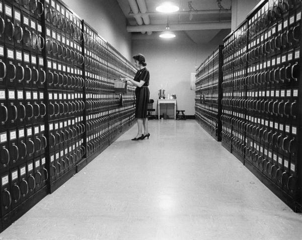 A clerk checks real estate property information in a vast filing system housed in a vault.