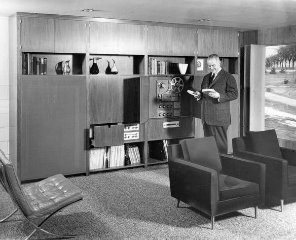 Urbane gentleman shows off his sophisticated high fidelity wall system with reel-to-reel tape deck, reels of tape, and record albums.
