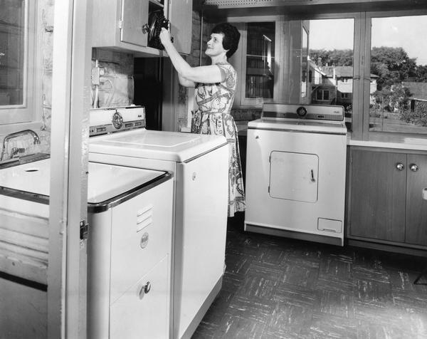 A housewife shows off her newly-installed laundry room.