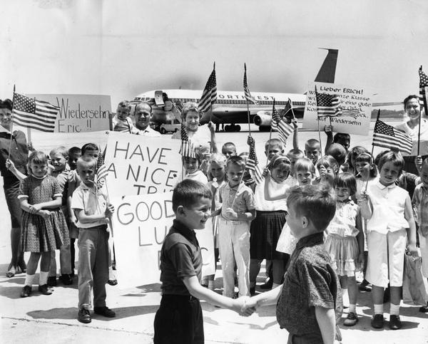 Children, adults, and a Northwest Airlines Boeing 707 jetliner on the tarmac at General Mitchell International Airport. The children, all first graders from Happy Hollow School, were on a field trip to say farewell to a classmate who was about to depart with his mother to visit relatives in West Germany. Milwaukee had entered the jet age only two years earlier with the arrival of a Northwest Airlines Boeing 720.