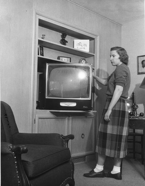 A young woman is displaying a television set.