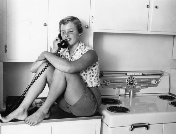 A kitchen counter is a good perch for a teenage girl's telephone conversation.