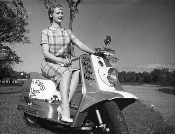 A motor scooter in an advertisement with female model sitting on a Cushman Road King motor scooter.