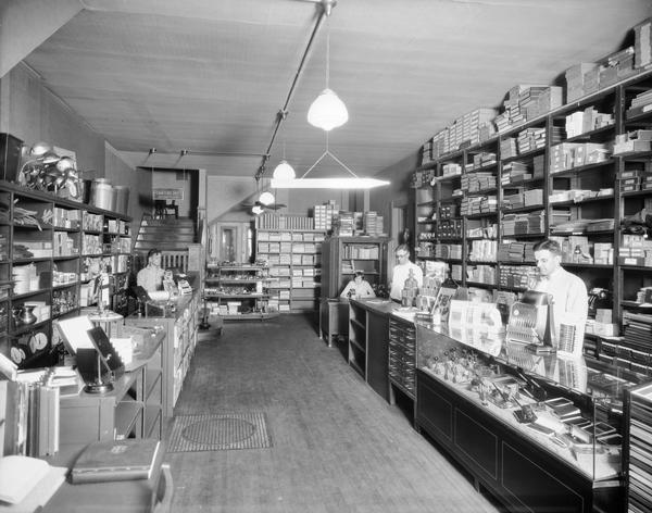 The interior of the first floor of Blied Office Supplies Store. Three men and a women are behind counters and a desk.