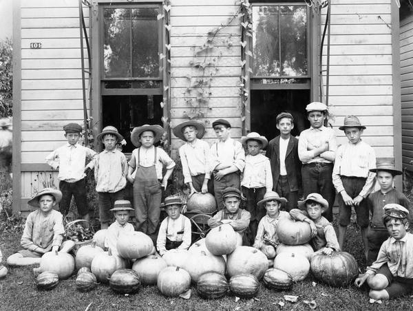 Group of young boys, all wearing hats, posed in front of a building with an assortment of pumpkins and watermelons.