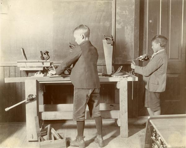 Two boys of different ages using wood tools, including planes and files, during a classroom exercise.