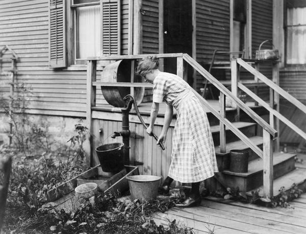 Woman pumping water from a well near the porch of her farmhouse.