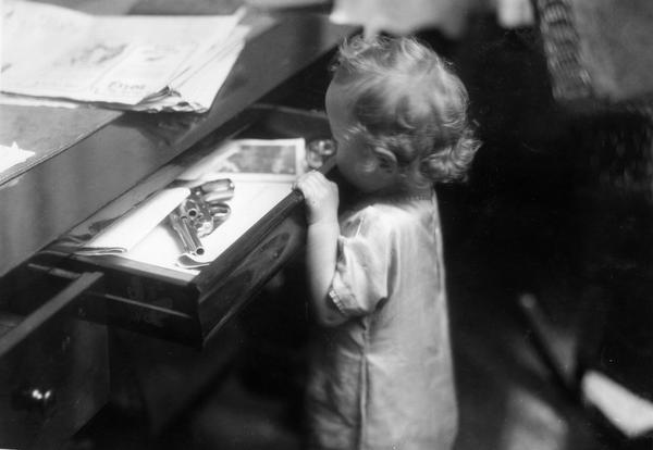 "Small child opening a desk drawer containing a shining revolver (hand gun). The scene was staged for International Harvester's Agricultural Extension Department. The photograph was used to warn families of potential farm hazards. The original caption reads: ""the revolver in desk drawer is in a bad place."""