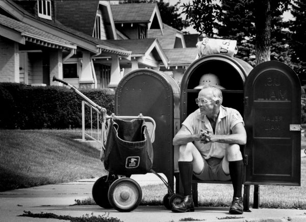 A male mail carrier takes a break sitting in a mailbox on the sidewalk in a neighborhood.