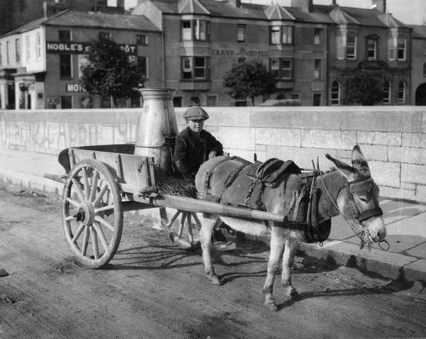 A young boy drives a donkey-powered cart with a large milk can as cargo in Fermoy, Ireland.