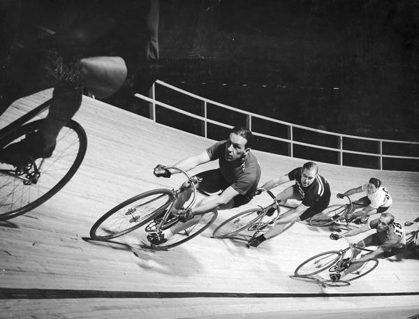 Group of racers bank around a turn on a velodrome track.