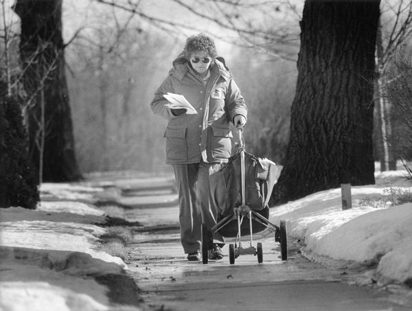 A woman mail carrier pushes her cart with a full mailbag along a sidewalk edged by snowy lawns.