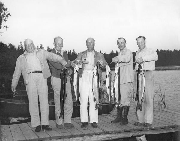 Dwight D. Eisenhower, fishing with his brothers on Wisconsin Lake, proudly exhibit Muskies and one Northern Pike.