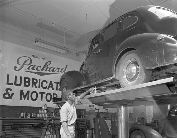 An African American mechanic works on a car up on the rack for servicing at the gas station Meehan Motor Mart, 209 East Washington Avenue.