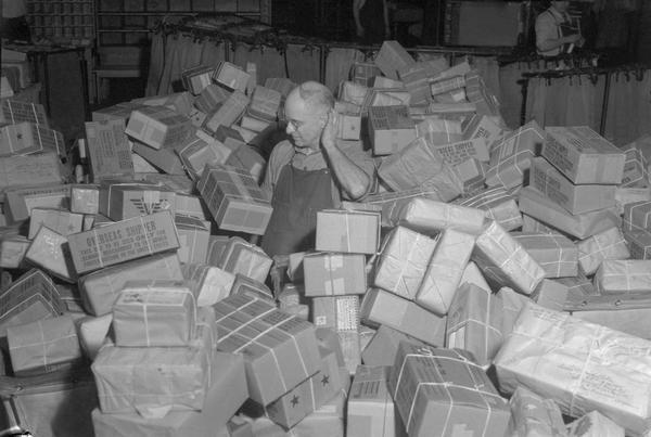 Fred Boyle, clerk at the post office, looks overwhelmed surrounded by a mountain of Christmas parcels to be sorted for shipment overseas to men and women in service.