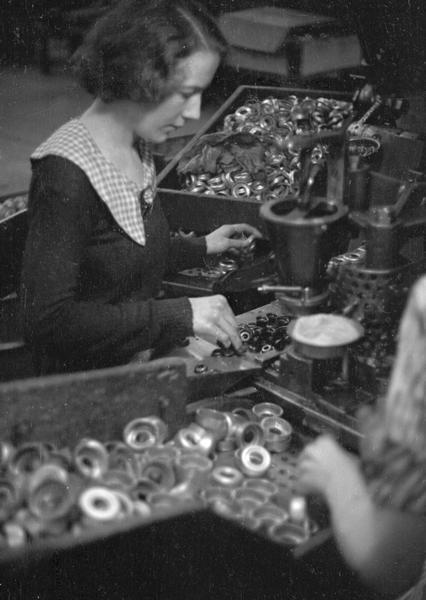 A woman factory worker sorting parts at Globe Union Manufacturing Company, maker of batteries, radio apparatus, and spark plugs.