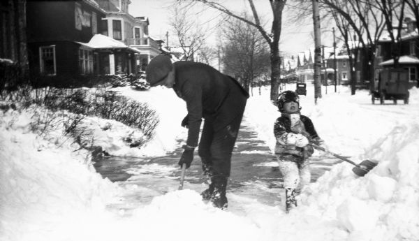 Winter scene with a man and young boy shoveling snow from a sidewalk after a heavy snowfall.
