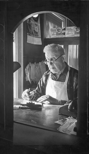 William Behnke goes over bills in his office at the rear of his store, which was in business since July 12, 1899.