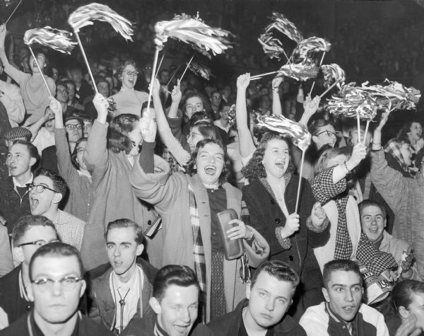 High school fans in the bleachers cheer on their team during a night game.