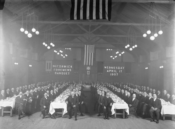 "Large group of men sitting and posing at long dining tables in the Club House of International Harvester's McCormick Works factory. The men are attending the ""McCormick Foreman's Banquet."""