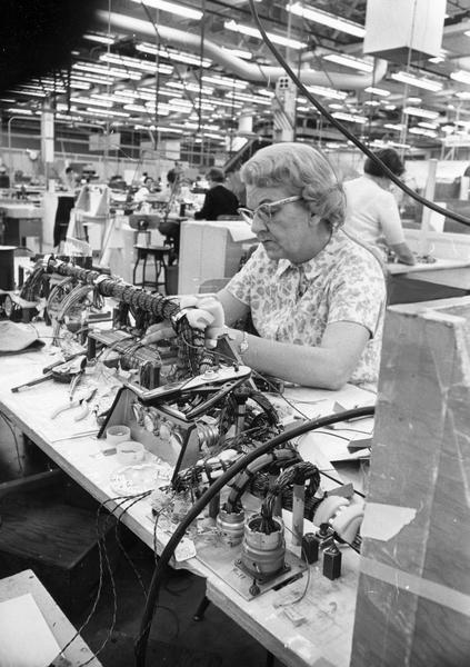 Woman working on a wire harness for the lunar module section of an Apollo spacecraft at the AC Electronics division of General Motors Corp. plant.
