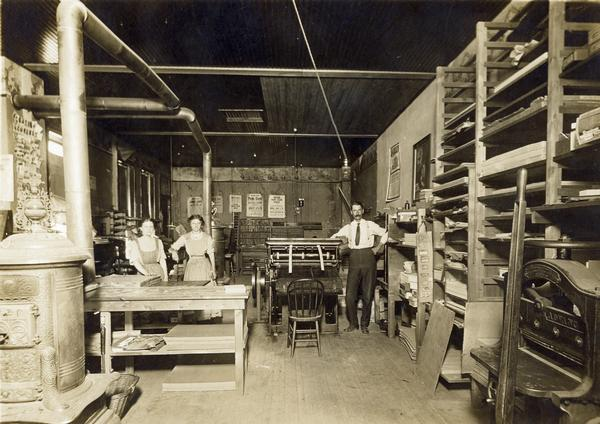 Interior view of the Brillion News Print Shop, where a printer and his assistants, two women, are posing around a press and work tables.