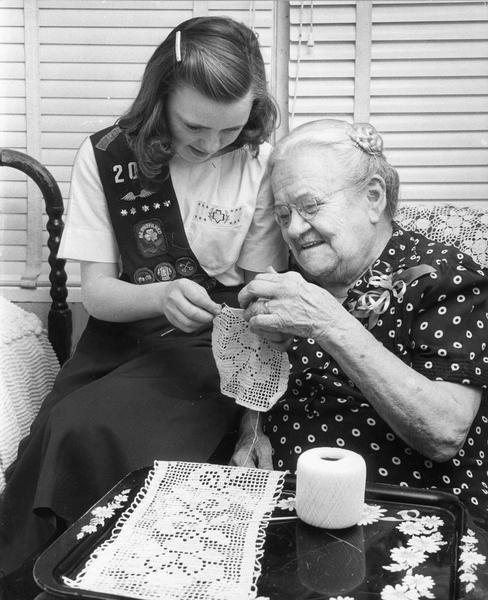 "A Girl Scout crocheting doilies at a senior citizens' care center with her ""adoptive grandmother."""