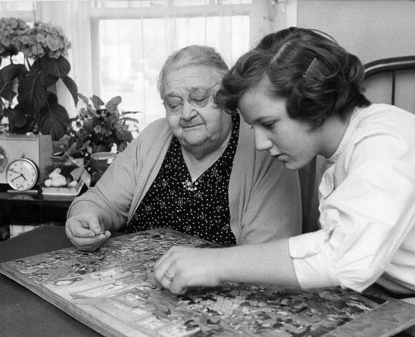 "An elderly woman, Josephine Fell, is the ""adopted grandmother"" to a Girl Scout that visits her and works with her on a puzzle at Rosemary's Nursing Home in Madison."