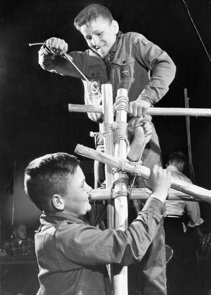 Boy Scouts lash together lengths of wood as they put up an exhibit about pioneering for Scout-O-Rama.