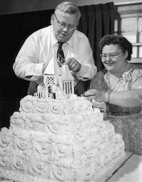 Mr. and Mrs. Wallace Braatz top off the 26-layer wedding cake that Mrs. Braatz made for their daughter's wedding.