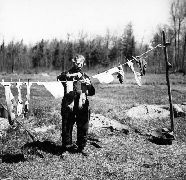 In a photograph taken for the Farm Security Administration, a man hangs socks to dry on a clothesline on land where trees have been cut down, or cutover.