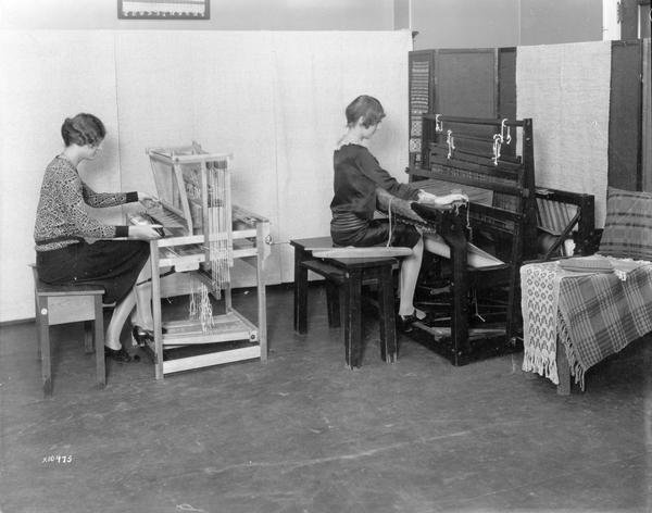 Two women weave at looms in a University of Wisconsin class.