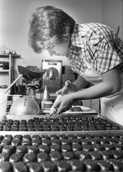 Jim Niemann decorates dipped chocolates at his family's business, Niemann's Home Made Chocolate Shop.