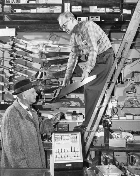Hilgendorf's Hardware store clerk shows a saw to a customer.