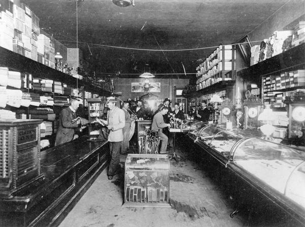 Customers receive assistance from clerks inside a general store.