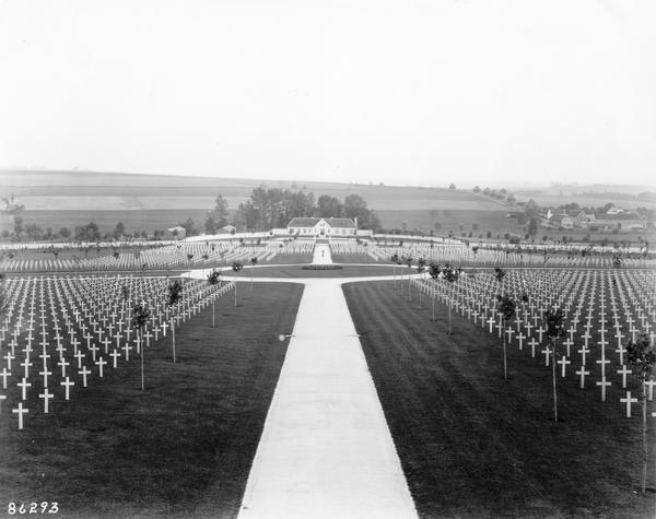 A backdrop of farmland frames small white crosses arranged in a cemetery in France after World War I.