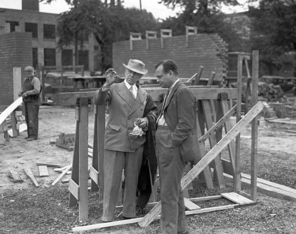 Frank Lloyd Wright conferring with another man on the site of one of his great designs, the Johnson Wax Building.