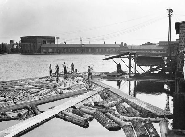Workers push logs floating in the Wisconsin River into alignment to enter a building for processing.