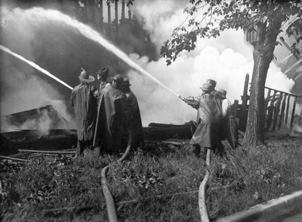 Fire fighters standing amid smoking timbers aim their hoses to douse the flames.